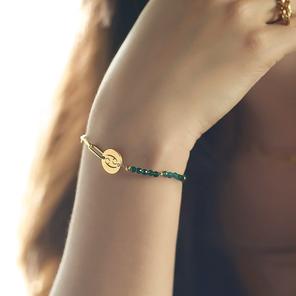 Woman wearing a gold zodiac bracelet with her star sign on it