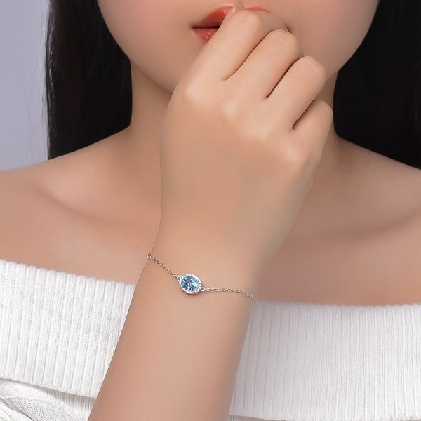 Sterling silver bracelet with a blue oval cut topaz on a woman's wrist
