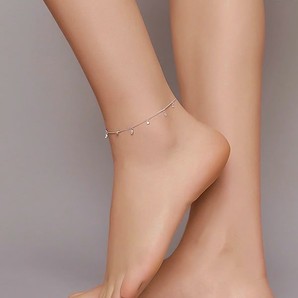 Silver crystal charm anklet displayed on a womans ankle