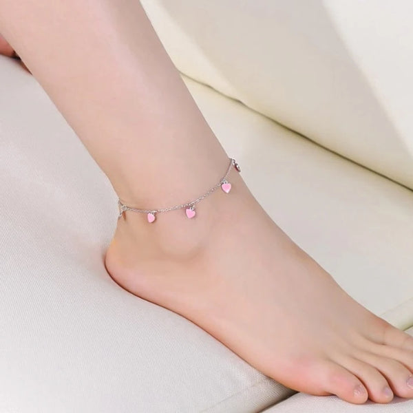 Womans ankle displaying a silver pink hearts charm anklet