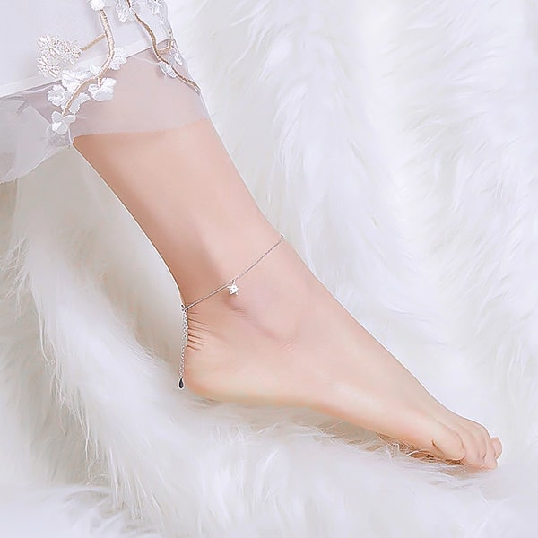 Silver star anklet on a womans ankle