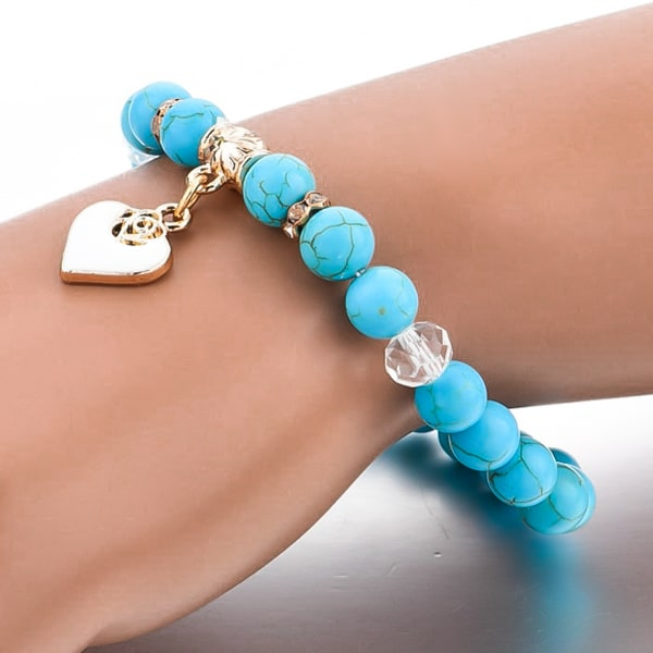 Woman wearing a beaded turquoise stone bracelet with a gold heart charm