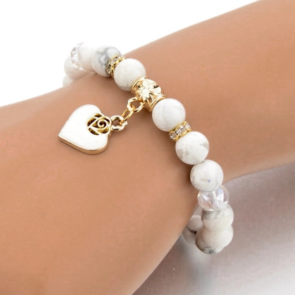 Woman wearing a beaded white marble bracelet with a gold heart charm