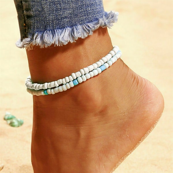 White handmade beaded anklet on a womans ankle
