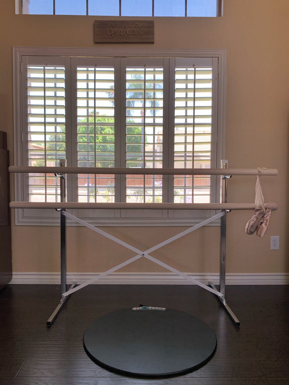 free standing adjustable ballet barre with dot2dance in front and pair of pointe shoes hanging off it