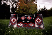 Contour Fall Harvest Saddle Pad in black, red, and gray with diamond pattern and black leather placed in a field