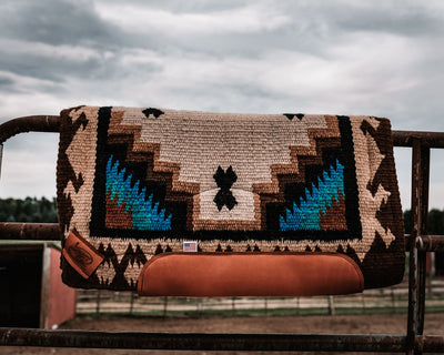 Straightback Haymaker Woven Saddle Pad in tan, brown, and teal resting on a fence