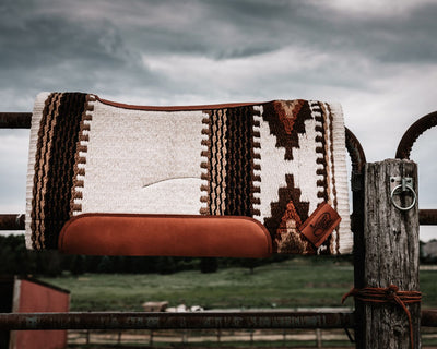 Contour Summer Cowtown Woven Saddle Pad- Cream and brown resting on a fence