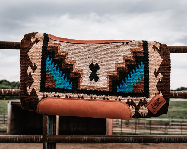 Contour Haymaker Woven Saddle Pad in tan, brown, and teal resting on a fence