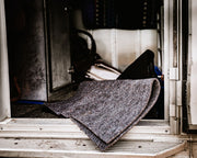 Gray saddle pad liner set in a trailer