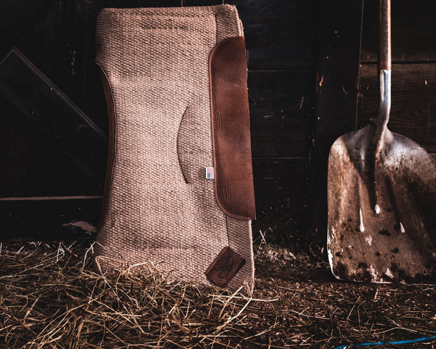 Contour Spring Woven Saddle Pad- sand color with brown leather placed in a barn next to a shovel