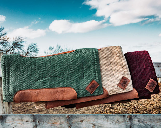 Three Contour Spring Woven Saddle Pad resting on a wood fence