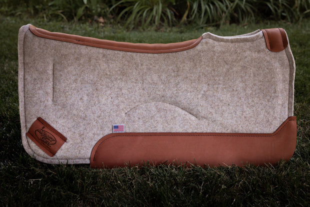 Contoured saddle pad in tan felt with burnt orange colored leather  standing up in a field of grass