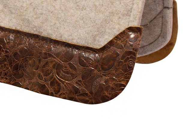 Close up of brown floral wear leather on a tan felt saddle pad