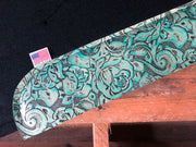 Close up of teal floral wear leather on black saddle pad laid on a pallet