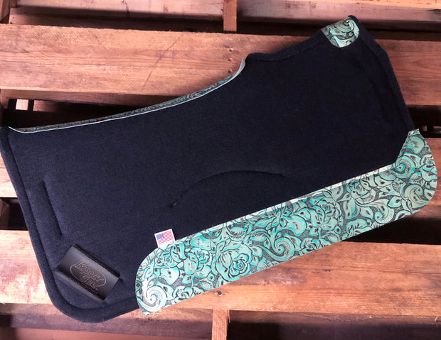 Black saddle pad with teal floral leather laying on pallet