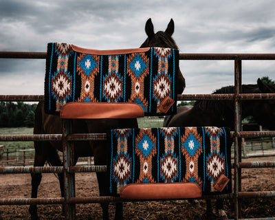 Contour Cut and Straightback woven Aztec Dreamer Saddle pads in blue, tan, and black on a fence with two horses in the background.