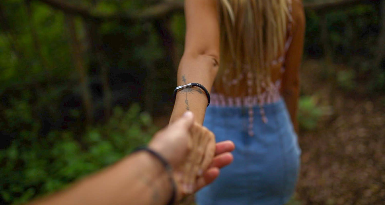 Couple holding hands wairing bracelets