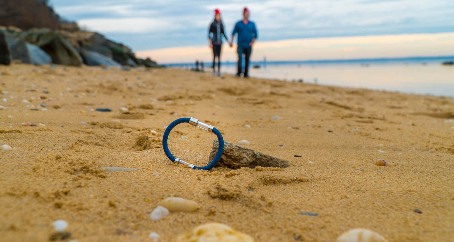 couple walking on the beach with the arctic bracelet laying in the sand