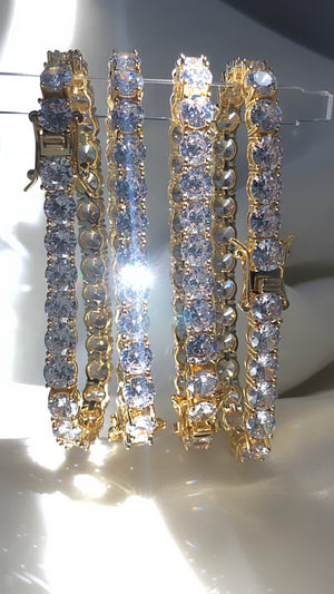 Tennis Bracelet  High Grade AAAAA Cz (Simulated diamonds)  Available in 7 inches or 7.5 inches ( Please measure wrist before purchasing/ all sales are FINAL )  7mm  14k Gold Plated  Gold Setting  Extremely High quality Brass ( Please keep away from water and fragrances to maintain shine )  Each Bracelet Sold Separately.