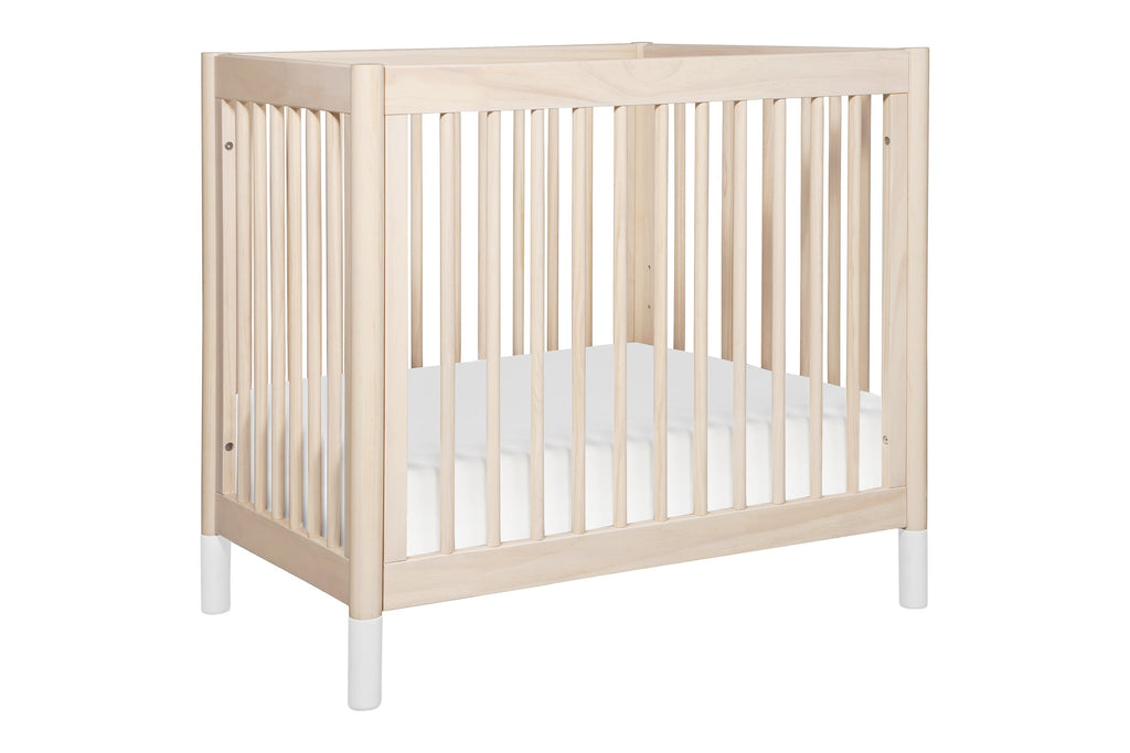 M12998NXW, Gelato 2-in-1 Mini Crib in Washed Natural with White Feet at angle