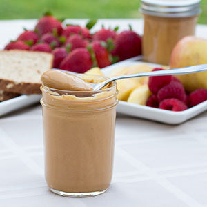 Coconut Peanut Butter spooned out of jar with fruit and bread in background | Aloha Spreads
