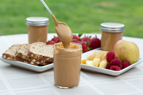 Spoonful of Coconut Peanut Butter out of jar with fruit and bread - Aloha Spreads