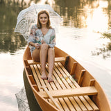 young girl in a boat under lace umbrella