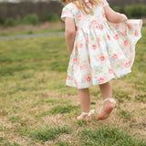 little girl in a flower pattern dres playing in the backyard
