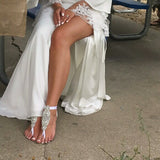 Beach wedding bride wearing long dress and crystal statement barefoot sandals