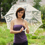 Girl under the ivory lace wedding umbrella