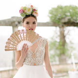 Bride wearing flower crown and holding gold lace hand fan