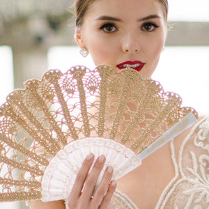 Gold bridal hand fan in young bride hand
