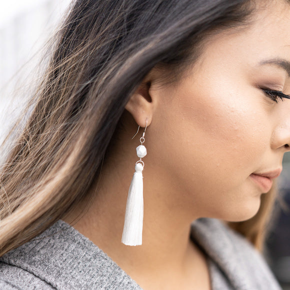 Beautiful girl wearing long dangle white marble tassel earrings