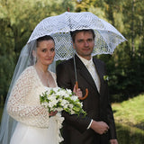 Bride and groom under white lace umbrella