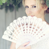 blond bride holding ivory lace hand fan