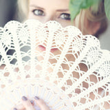bride hiden behind the ivory lace hand fan
