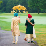 Hindu groom with his best man under yellow umbrella