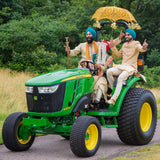 Hindu groom with his best man under yellow umbrella on a tractor