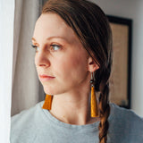 Girl by the window, wearing Ochre Brown Long Dangle Tassel Earrings