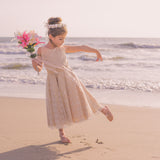 Beach wedding flower girl dancing on the beach