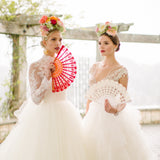 2 Spanish brides wearing flower crowns and holding lace hand fans in red and ivory