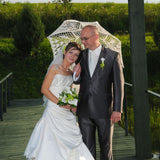 Bride and groom under the lace wedding umbrella