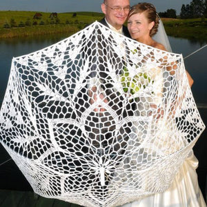 Newlyweds with a lace wedding umbrella
