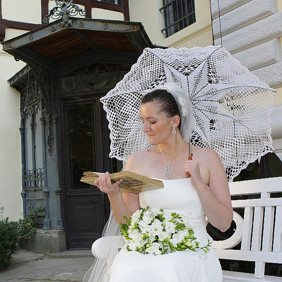 Reading bride under the lace umbrella