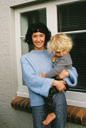 Eleanor at home wearing the hej hej What Now Whatnall knit.