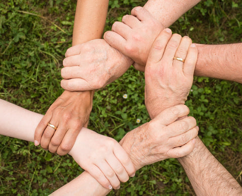 hands in a circle as a team of essential tremor sufferers