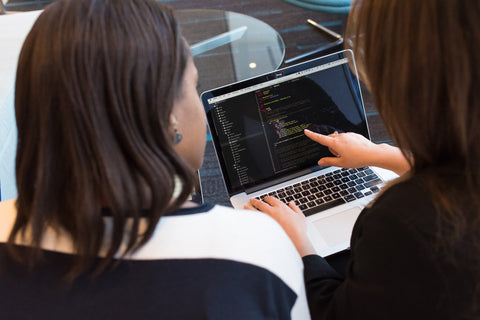 Two women discuss coding on a website