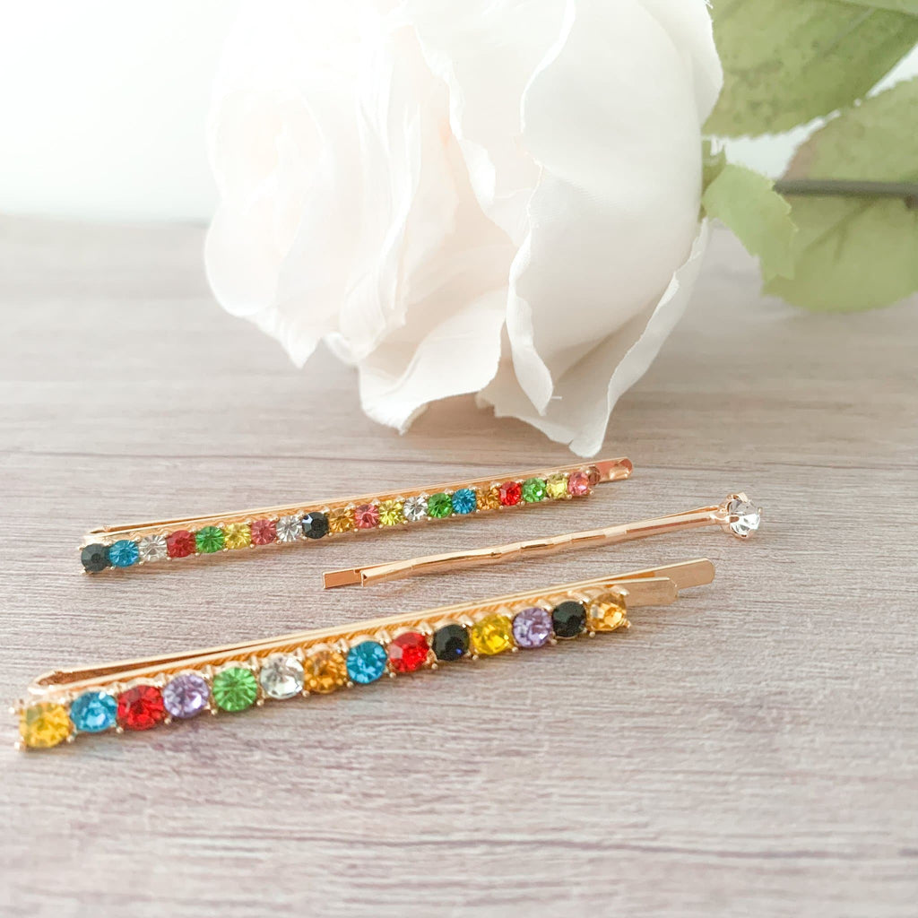Set of 3 Bobby Pins Shot on wood floor with a rose next to it.  Set includes two rainbow colored rhinestone bobby pins and one gold bobby pin with a single crystal at the end.