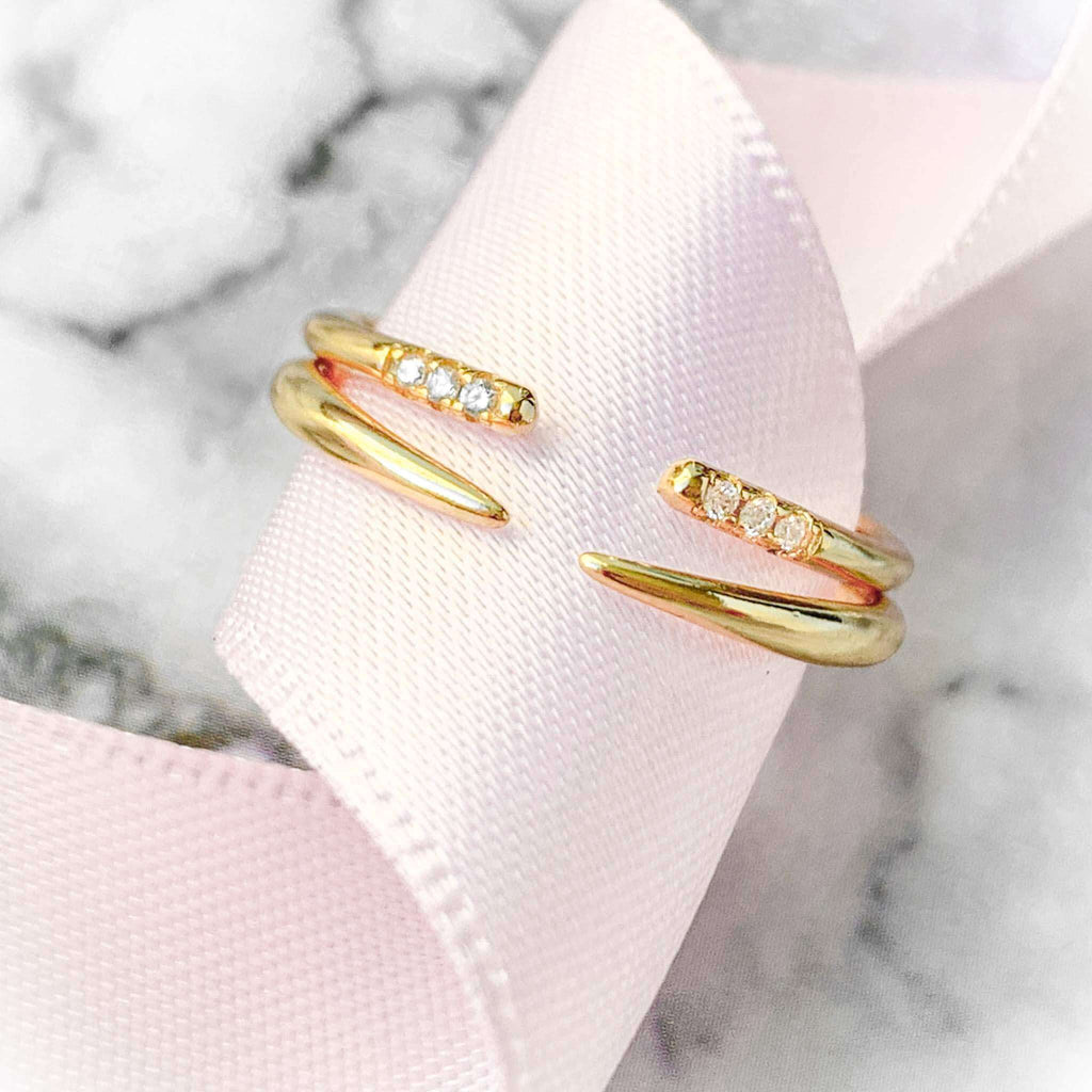 Close up of Austin Gold Open Claw Ring with 3 Pave Stones next to Augusta Gold Open Claw Ring. Rings are wrapped around a curled up pink ribbon shot on a marble tile.